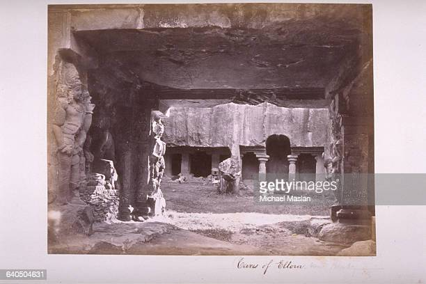 A doorway cut through solid rock and decorated with highrelief sculptures opens into a courtyard within the Caves of Ellora an extensive network of...