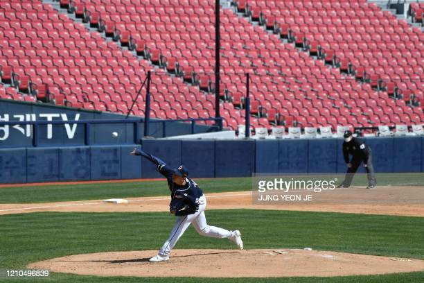 Doosan Bears pitcher Lee Youngha throws a ball in front of empty stands as a referee wearing a face mask looks on during a preseason baseball game...