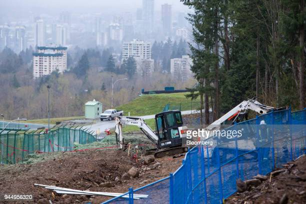 A Doosan Bobcat Inc compact excavator and bulldozer sit at the Kinder Morgan Inc Trans Mountain pipeline expansion site in Burnaby British Columbia...