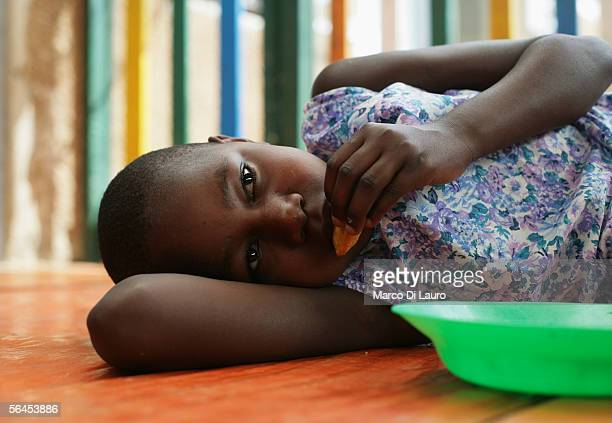 Dora an HIV positive orphan eats lunch on the floor of the Aidchild Orphanage on December 6 2005 in Mpigi 60 km north of the capital Kampala Uganda...