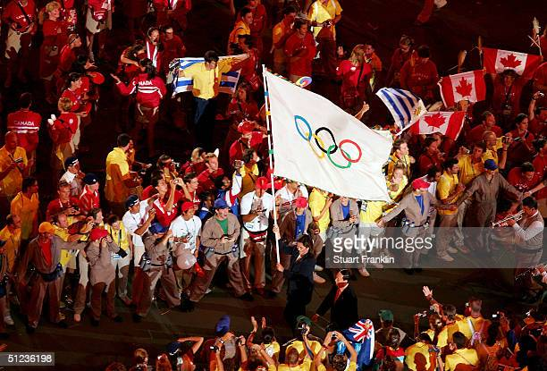 Dora Bakoyianni, mayor of Athens, carries the Olympic flag as she walks next to Wang Qishan, mayor of Beijing, the host city of the Games of the XXIX...