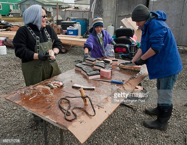 Dora Brower cuts up muktuk with her nephews in her yard in Barrow The whale had been caught in the fall and had been seasoning over the winter in...