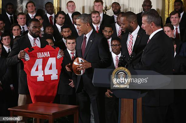 Doran Grant of the Ohio State University Buckyes football team presents US President Barack Obama a team jersey as teammate Curtis Grant and head...