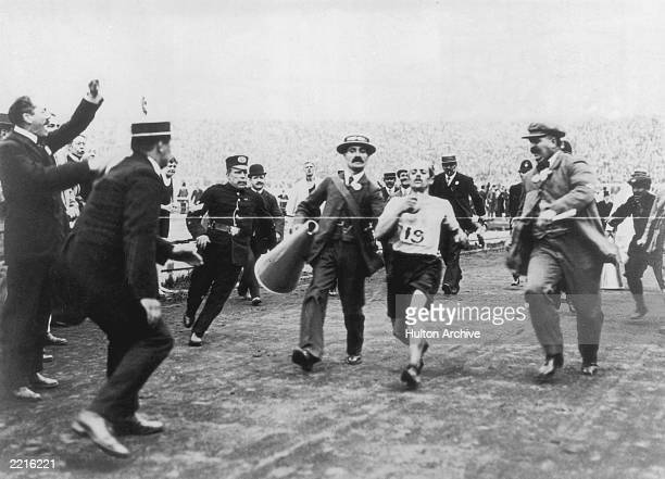 Dorando Pietri of Italy on the verge of collapse is helped across the finish line in the Marathon event of the Olympic Games in London 24th July 1908...
