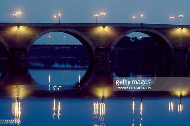 Dordogne, France - A view of the town of Bergerac at night: bridges with their reflections in the river.