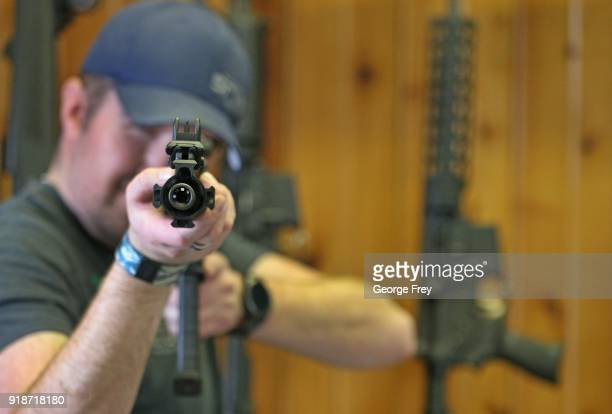 Dordon Brack, aims a semi-automatic AR-15 that is for sale at Good Guys Guns & Range on February 15, 2018 in Orem, Utah. An AR-15 was used in the...