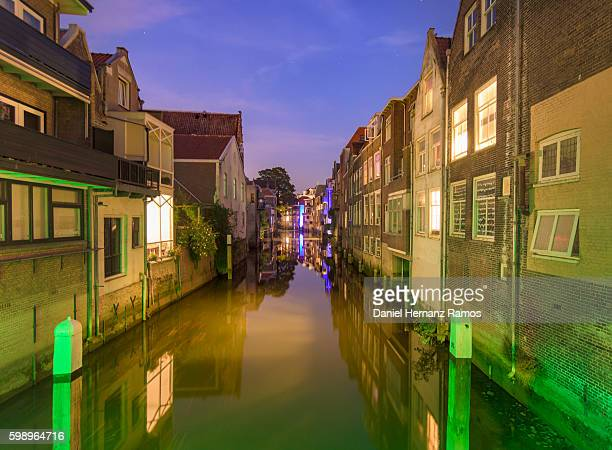 Dordrecht reflection of houses in the canal at dusk. Empty street