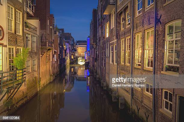 Dordrecht reflection of houses in the canal at night. Empty street