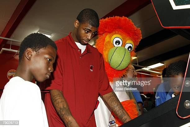 Dorell Wright of the Miami Heat and the Miami Heat Mascot Burnie play pinball with children during the unveiling of the Heat Learn Play Center on...