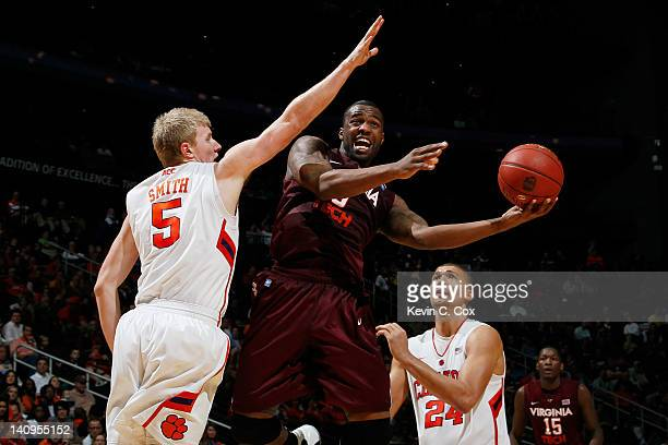 Dorenzo Hudson of the Virginia Tech Hokies shoots between Tanner Smith and Milton Jennings of the Clemson Tigers in the second half of their first...