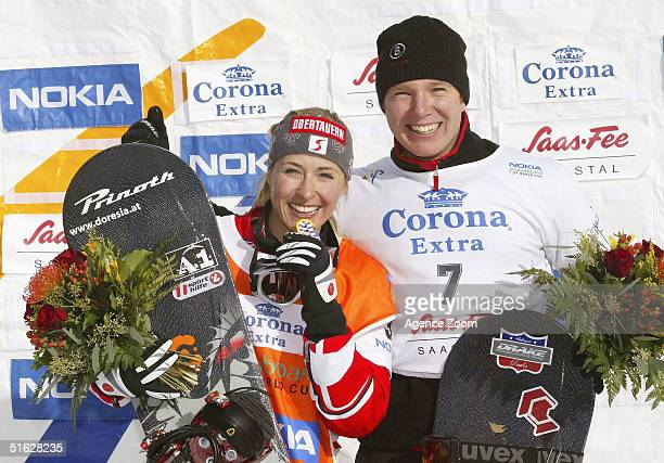 Doresia Krings of Austria celebrates victory in the FIS Womens World Cup Snowboardcross Event with the winner of the Mens event Michael Layer of...