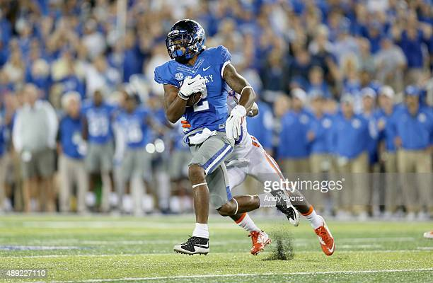 Dorian Baker of the Kentucky Wildcats runs with the ball while defended by Marcus Maye of the Florida Gators at Commonwealth Stadium on September 19...