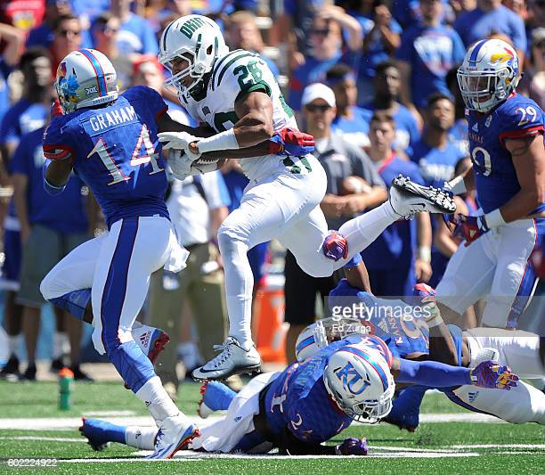 Dorian Brown of the Ohio Bobcats picks up yards against Chevy Graham Bazie Bates IV and Brandon Stewart of the Kansas Jayhawks in the first quarter...