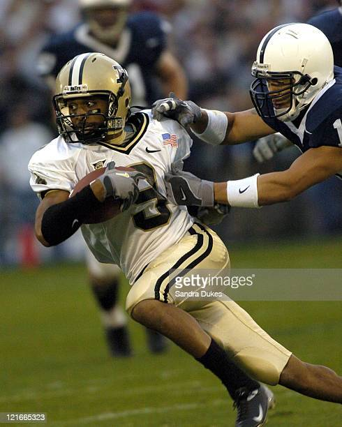 Dorian Bryant looks for room to run in the grasp of Andrew Guman after catching a pass in traffic in Purdue's 2013 win at Beaver Stadium State...