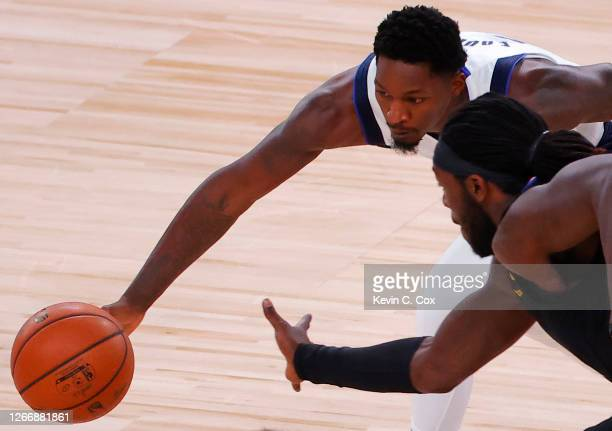 Dorian FinneySmith of the Dallas Mavericks and Montrezl Harrell of the LA Clippers reach for a loose ball during the second quarter in Game One of...