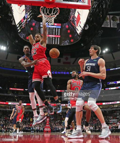 Dorian Finney-Smith of the Dallas Mavericks passes around Daniel Gafford of the Chicago Bulls to teammate Boban Marjanovic at the United Center on...