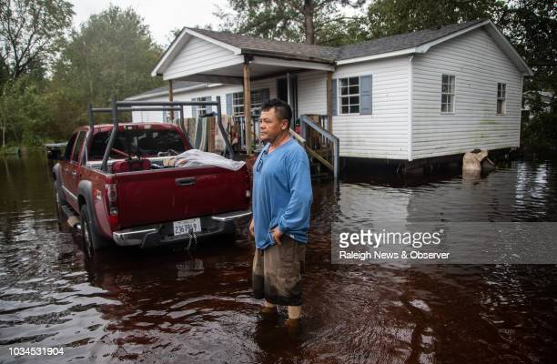 Dorian Gallegos helps his family move out of a flooded home on Will Baker Road in Kinston on Sunday, Sept. 16, 2018 following the aftermath of...