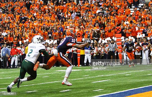 Dorian Graham of the Syracuse Orange can't complete the catch as hes chased by Quenton Washington of the South Florida Bulls during the game at the...