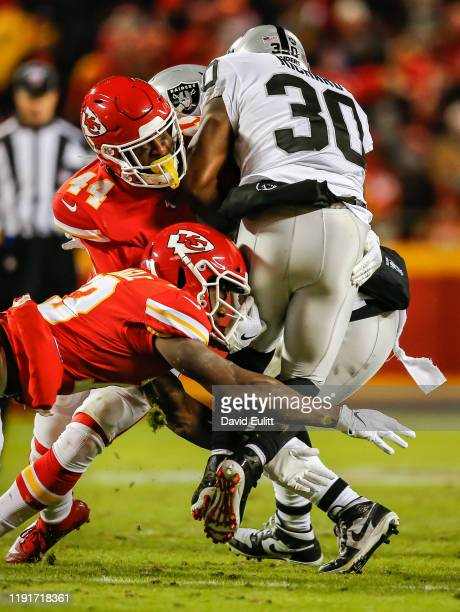 Dorian O'Daniel of the Kansas City Chiefs and Byron Pringle of the Kansas City Chiefs tackle Jalen Richard of the Oakland Raiders on a third quarter...