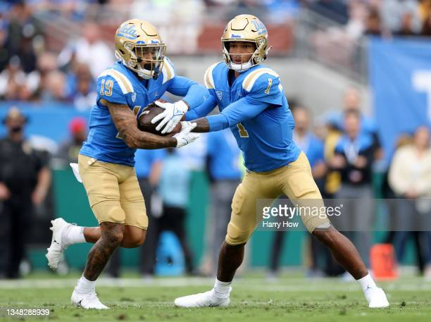 Dorian Thompson-Robinson of the UCLA Bruins hands off to Kazmeir Allen during the first half against the Oregon Ducks at Rose Bowl on October 23,...