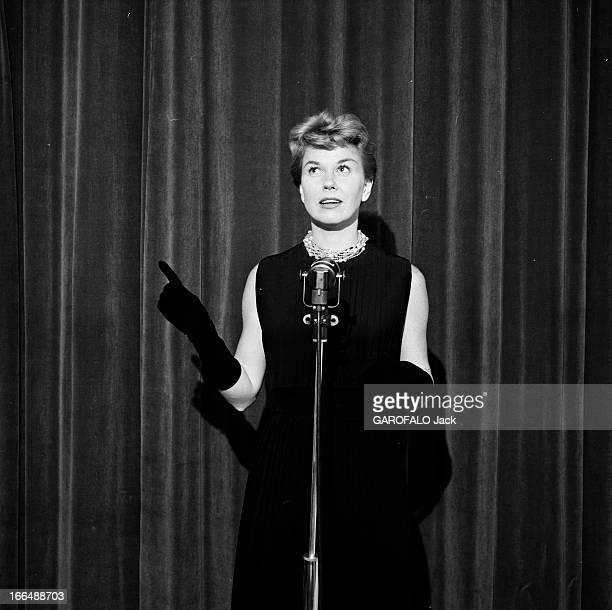 Doris Day En avril 1955 Doris DAY en visite à Paris Sur scène devant le rideau l'actrice vêtue d'une robe sans manches face à un micro