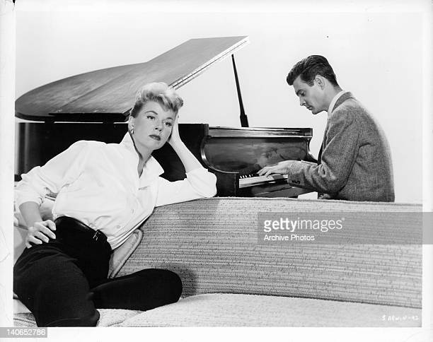 Doris Day listens as Louis Jourdan plays the piano in a scene from the film 'Julie' 1956