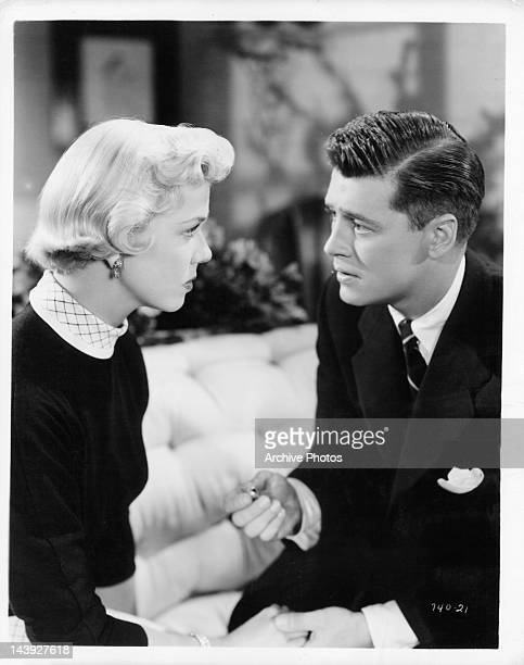 Doris Day looking at Gordon MacRae as he holds her hand in a scene from the film 'Tea For Two' 1950