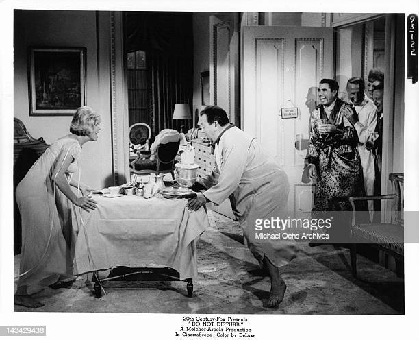 Doris Day pushing a room service table away from her in a scene from the film 'Do Not Disturb' 1965