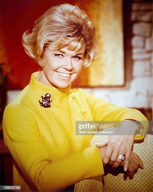 Doris Day US actress and singer smiling and wearing a yellow highneck jacket with a brooch on the right shoulder in a studio portrait circa 1965