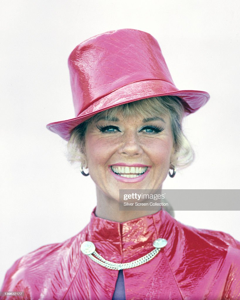 Doris Day, US actress and singer, wearing a bright pink hat and matching cape, fixed at the neck with a silver chain, circa 1970.