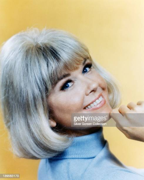 Doris Day US actress and singer wearing a light blue polo neck jumper smiling with her chin resting on her right hand in a studio portrait against a...