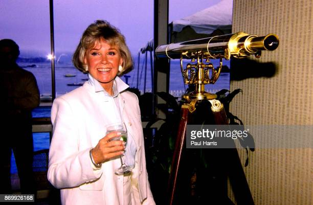 Doris Day with a telescope and a glass of wine at a press conference at the dog friendly hotel she owns in Carmel California July 16 1985