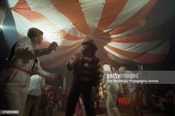 Doris Delay dressed in a white jumpsuit dances with a member of the Hell's Angels at the Acid Test Graduation During this celebration which was...