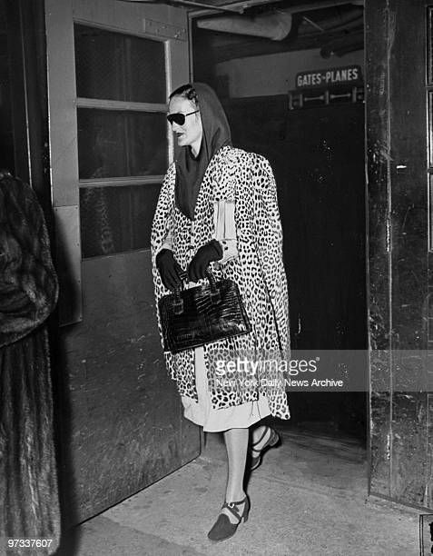 Doris Duke in a leopard skin coat sunglasses and scarf leaves Laguardia Field for her car after arriving nonstop from Los Angeles yesterday