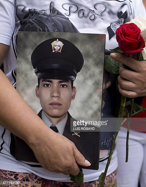 Doris Garcia Cardona mother of police officer Juan David Marmolejo holds his portrait during his funeral in Cali Valle del Cauca department Colombia...