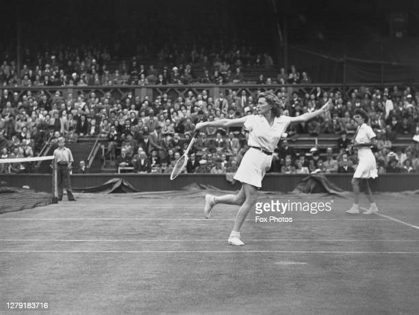 Doris Hart of the United States looks on as compatriot and doubles partner Pauline Betz reaches to make a backhand return to Louise Brough and...
