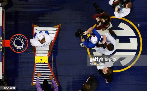 Doron Lamb of the Kentucky Wildcats celebrates by cutting down part of the net after they defeated the Florida Gators 70 to 54 during the...