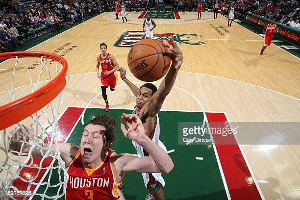 Doron Lamb of the Milwaukee Bucks grabs a rebound against Omer Asik of the Houston Rockets on January 4 2013 at the BMO Harris Bradley Center in...