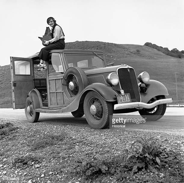 Dorothea Lange sits on the roof of a car, holding her camera. Lange is famous for her photographs of people hit hard by the Great Depression, such as...