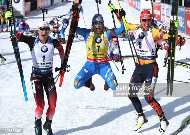 Dorothea Wierer of Italy celebrates victory next to Denise Herrmann of Germany and Marte Olsbu Roeiseland after the Women 10 km Pursuit Competition...