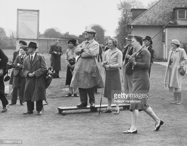 Dorothy Beck drives off the 1st tee watched by playing partner Diana Fishwick and spectators during the Daily Sketch War Relief Golf Tournament for...