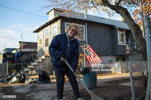 Dorothy Cavallero cleans the outside of her father's residence November 28 2012 in a residential area of New Dorp Beach in the Staten Island borough...