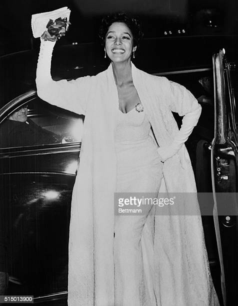Dorothy Dandridge star of film Carmen Jones waves to cameras on her arrival at Rivoli Theater for the premiere tonight The picture an adaptation of...