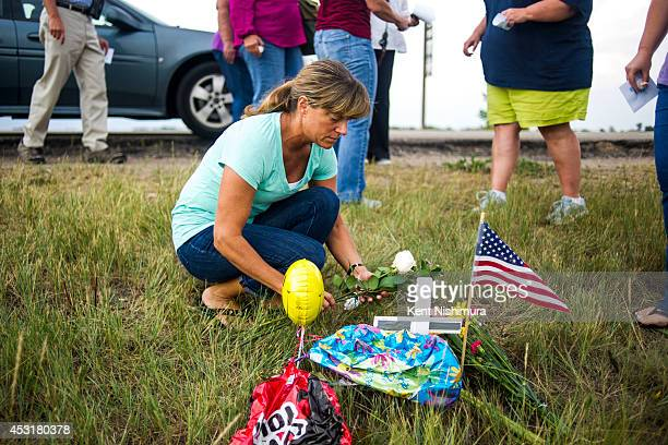 Dorothy Gibson places flowers at a small roadside memorial at an eagle's nest along E120th Avenue near E470 on Sunday July 27 2014 in Commerce City...