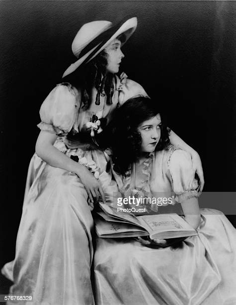 Dorothy Gish seated and holding book and Lillian Gish standing with arm around her circa 1920