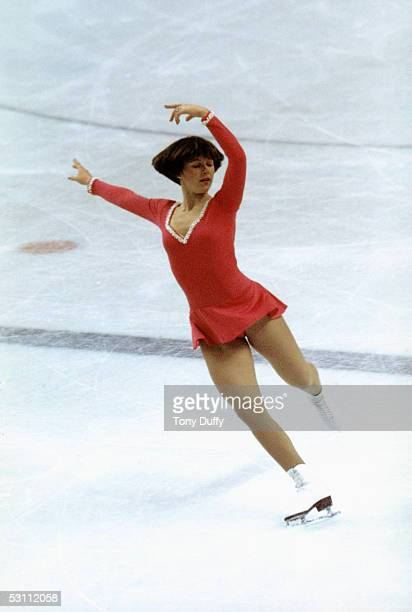 Dorothy Hamill skates on right skate with both arms posed above her head and left leg back during the Winter Olympics skating competition in 1976 in...