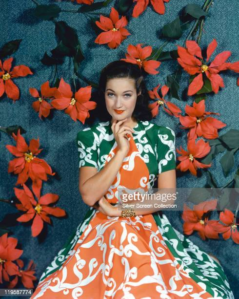 Dorothy Lamour US actress wearing a green and orange dress in a studio portrait against a blue background with red flowers 1940