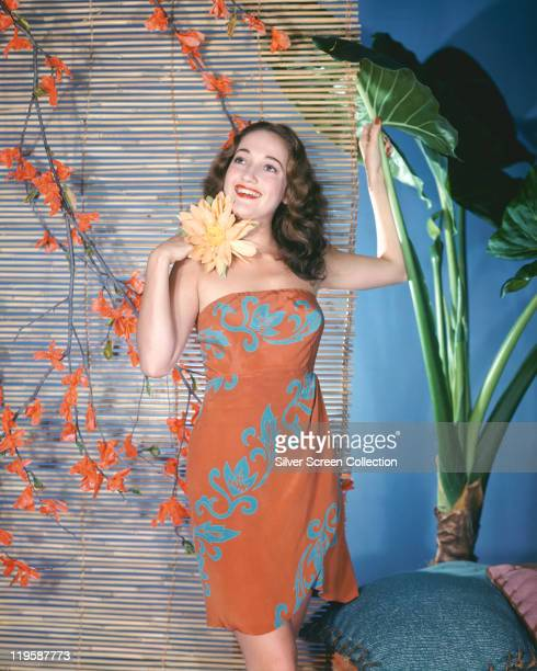 Dorothy Lamour US actress wearing a red and blue printed dress in a studio portrait holding a yellow flower to her neck 1940