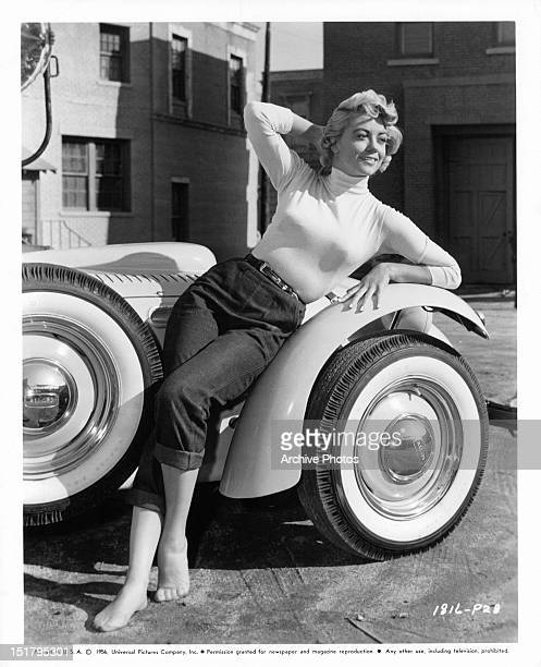Dorothy Malone poses on a car in publicity portrait from the film 'Written On The Wind' 1956