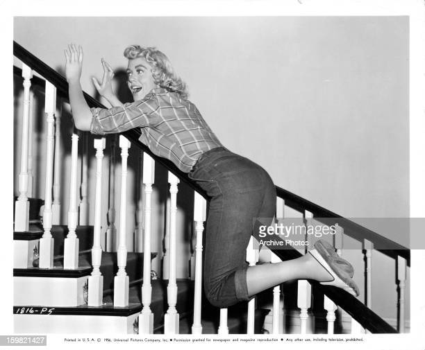 Dorothy Malone sliding down staircase railing in publicity portrait for the film 'Written On The Wind' 1956